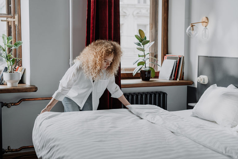 The significance of housekeeping management- A lady fixing the bed- Keezark